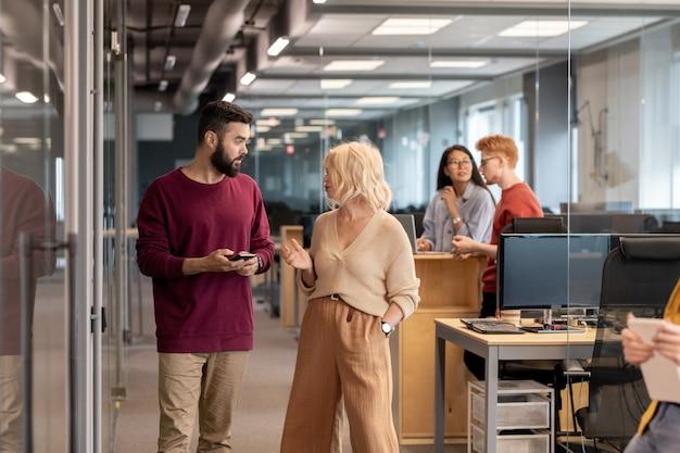 Jonge vertrouwen zakenman met smartphone luisteren naar zijn blonde volwassen vrouwelijke collega tijdens de bespreking van enkele ideeën