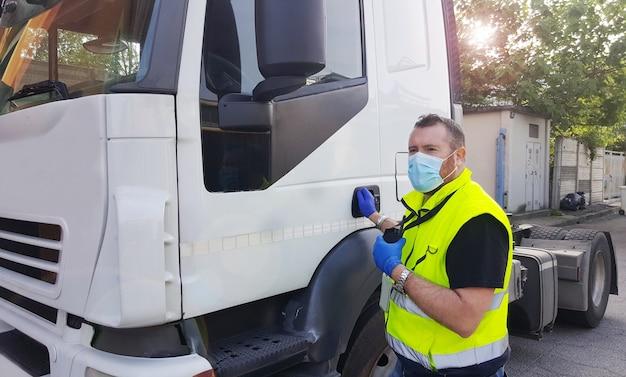 Jonge vervoerder op de vrachtwagen met gezichtsmasker en beschermende handschoenen