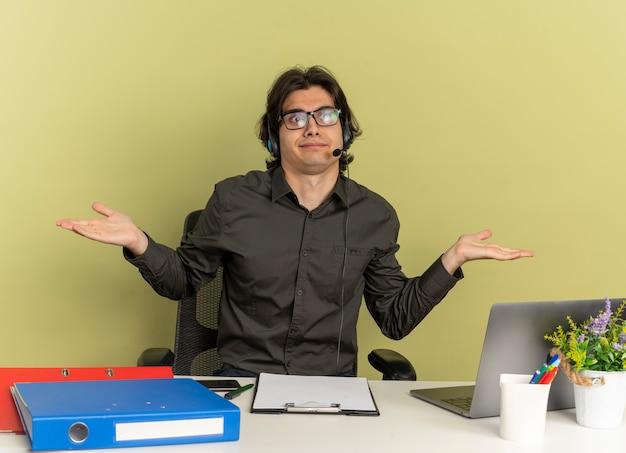 Jonge verward kantoor werknemer man op koptelefoon in optische bril zit aan bureau met office-hulpprogramma's die laptop gebruiken en kijken Gratis Foto