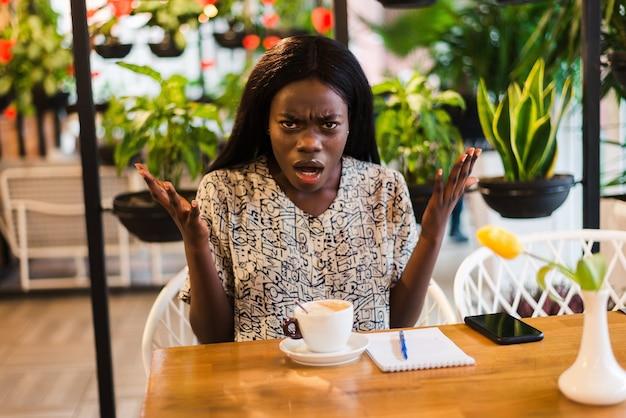 Jonge verwarde afrikaanse vrouw geschokt in coffeeshop