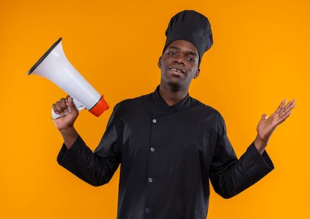 Jonge verwarde afro-amerikaanse kok in uniform chef houdt luidspreker en steekt hand op oranje met kopie ruimte