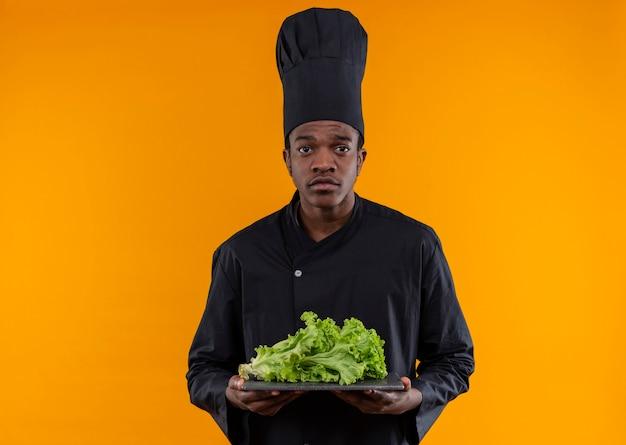 Jonge verwarde afro-amerikaanse kok in uniform chef houdt salade op snijplank geïsoleerd op oranje muur