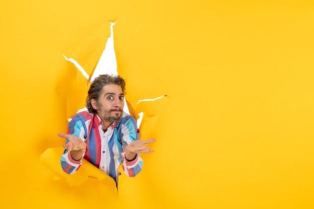 Jonge verwarde bebaarde man die voor de camera poseert door een gescheurd gat in geel papier