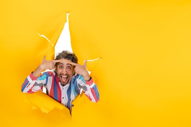 Jonge verwarde bebaarde man in een gescheurd gat en vrije ruimte in geel papier