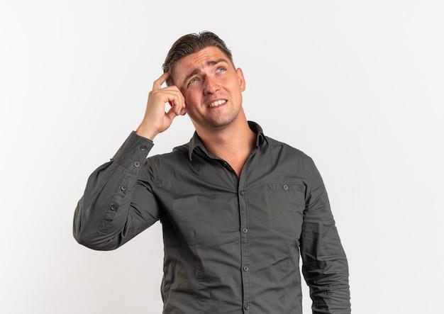 Jonge verwarde blonde knappe man legt vinger op hoofd opzoeken geïsoleerd op een witte achtergrond met kopie ruimte