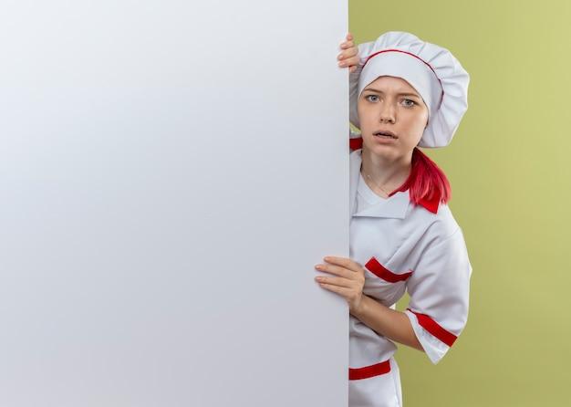 Jonge verwarde blonde vrouwelijke chef-kok in eenvormige chef-kok staat en kijkt achter witte muur die op groene muur wordt geïsoleerd
