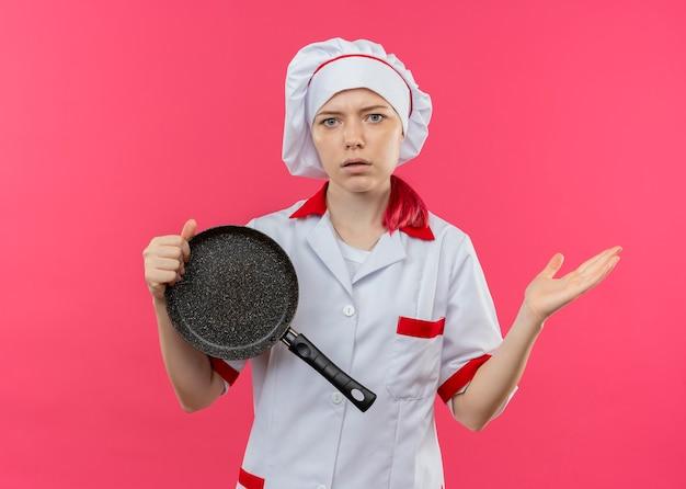 Jonge verwarde blonde vrouwelijke chef-kok in uniform chef houdt koekenpan en houdt hand open geïsoleerd op roze muur