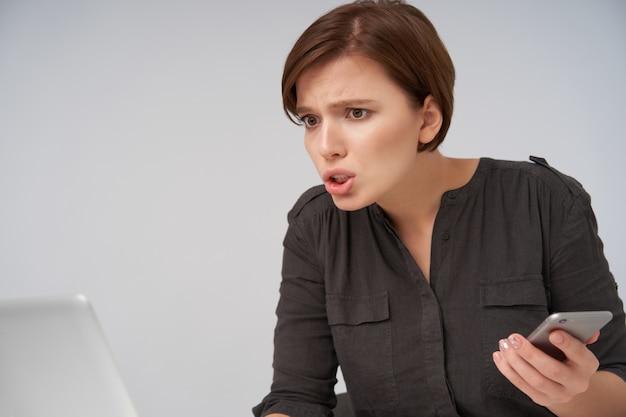 Jonge verwarde bruinogige mooie brunette dame met kort trendy kapsel houdt smartphone in opgeheven hand en fronsende wenkbrauwen terwijl ze voor zichzelf kijkt