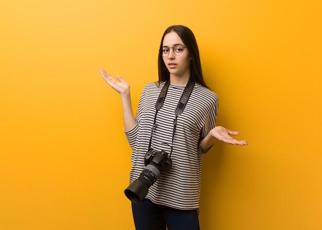 Jonge verwarde en twijfelachtige fotograafvrouw