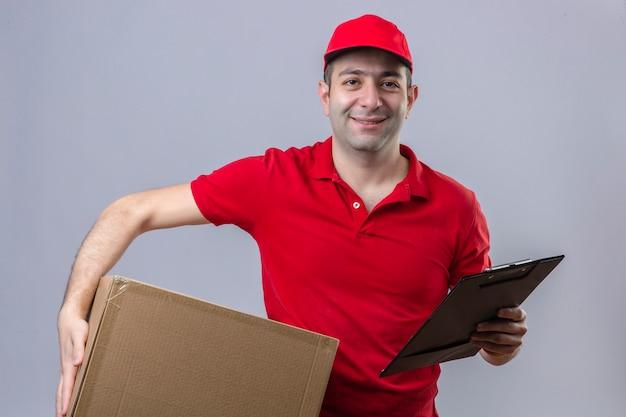Jonge verwarde leveringsmens in rood poloshirt en glb die zich met klembord en kartondoos bevinden in handen vriendschappelijk glimlachen over geïsoleerde witte muur
