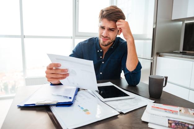 Jonge verwarde man die financiën thuis analyseert terwijl hij het hoofd met de hand vasthoudt en naar documenten kijkt