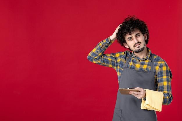 Jonge verwarde mannelijke server met krullend haar die een handdoek vasthoudt die de bestelling opneemt op geïsoleerde rode achtergrond
