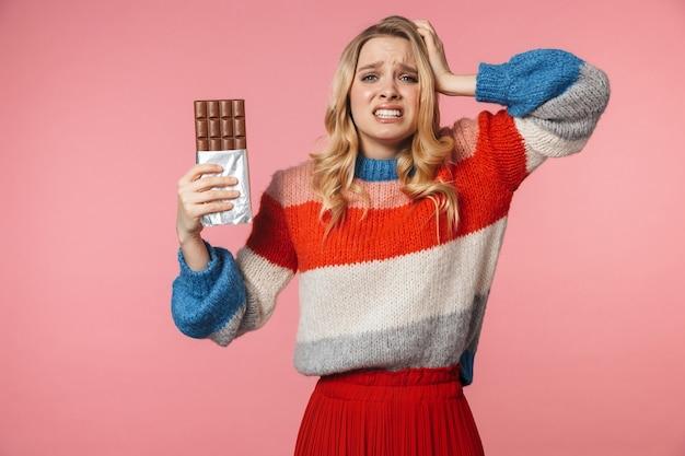Jonge verwarde nerveuze mooie mooie vrouw poseren geïsoleerd over roze muur met chocolade