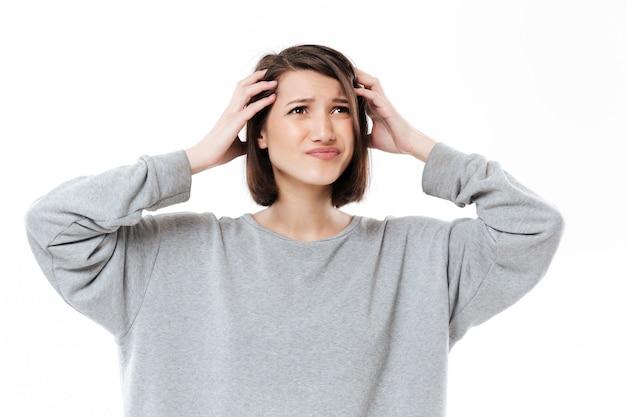 Jonge verwarde vrouw die haar handen op hoofd houdt