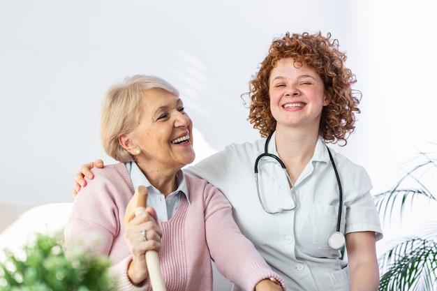 Jonge verzorger en senior vrouw lachen samen zittend op de bank.