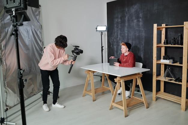 Jonge video-exploitant in vrijetijdskleding camera voor blogger met zwarte doos zitten door bureau in studio te houden