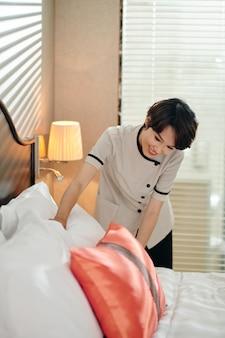 Jonge vietnamese meid die verse kussens op bed legt in hotelkamer