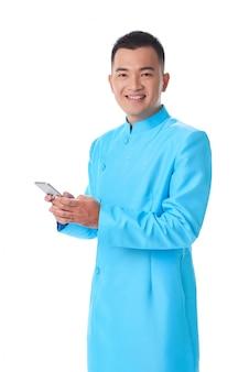 Jonge vietnamese mens in het traditionele kledij stellen in studio en het gebruiken van smartphone