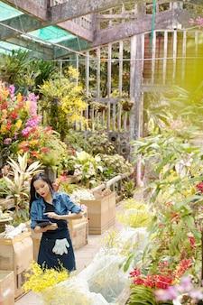 Jonge vietnamese vrouw die catalogus op tabletcomputer controleert bij het zoeken naar een bepaalde plant of bloem in kas
