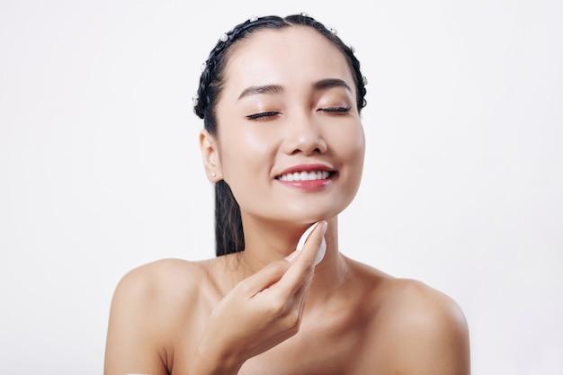Jonge vietnamese vrouw die haar gezicht afveegt met wattenschijfje gedrenkt in toner of kamille-extract