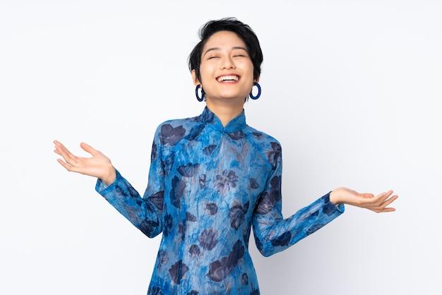 Jonge vietnamese vrouw die met kort haar een traditionele kleding over geïsoleerd wit draagt dat veel glimlacht
