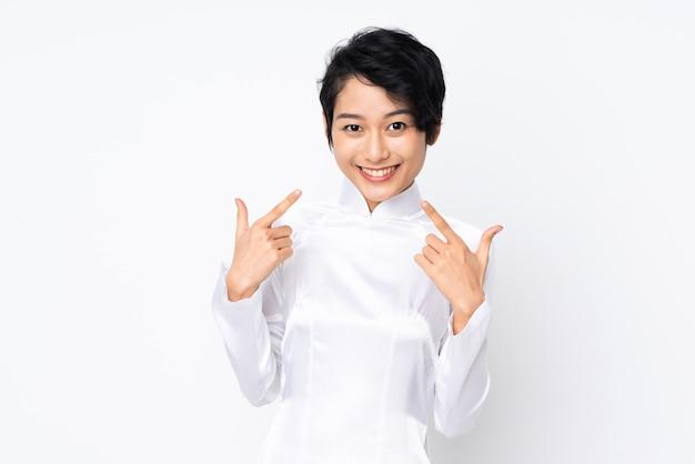 Jonge vietnamese vrouw met kort haar dat een traditionele kleding over geïsoleerd wit draagt dat duimen op gebaar geeft