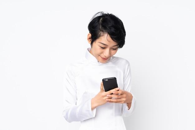 Jonge vietnamese vrouw met kort haar dat een traditionele kleding over geïsoleerd wit draagt dat een bericht met mobiel verzendt