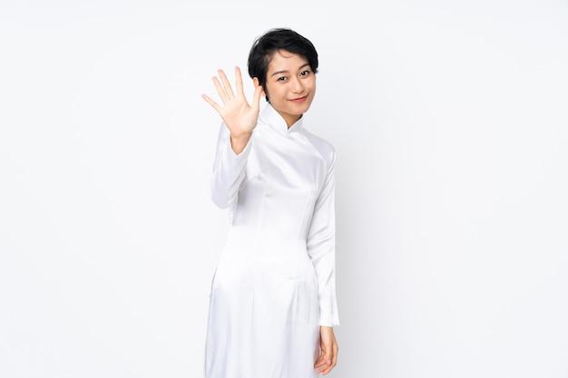 Jonge vietnamese vrouw met kort haar dat een traditionele kleding over geïsoleerd wit draagt dat vijf met vingers telt