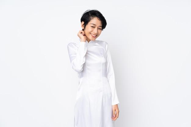 Jonge vietnamese vrouw met kort haar dat een traditionele kleding over het geïsoleerde witte lachen draagt