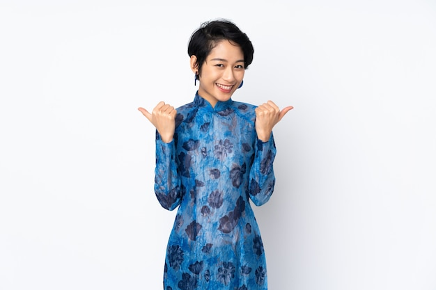 Jonge vietnamese vrouw met kort haar het dragen van een traditionele jurk over geïsoleerde witte muur met thumbs up gebaar en lachend