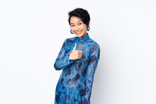 Jonge vietnamese vrouw met kort haar het dragen van een traditionele jurk over witte muur geven een thumbs up gebaar