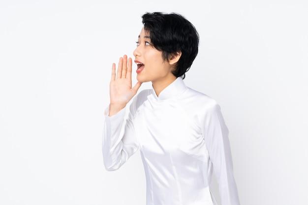Jonge vietnamese vrouw met kort haar het dragen van een traditionele kleding over geïsoleerde wit schreeuwen met mond wijd open aan de zijkant
