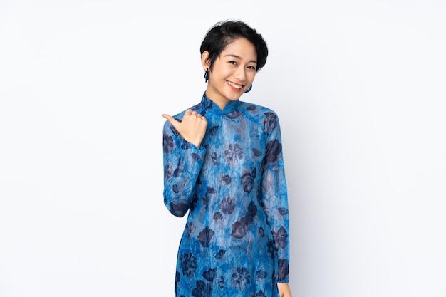 Jonge vietnamese vrouw met kort haar het dragen van een traditionele kleding over geïsoleerde wit wijzend naar de zijkant om een product te presenteren