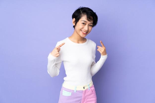 Jonge vietnamese vrouw met kort haar over paarse muur geven een duim omhoog gebaar