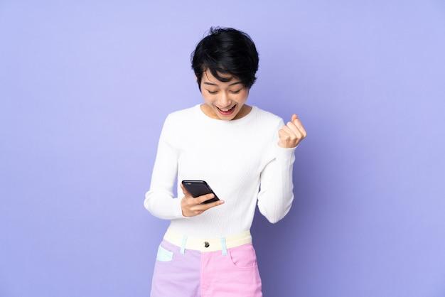Jonge vietnamese vrouw met kort haar over paarse muur verrast en het verzenden van een bericht