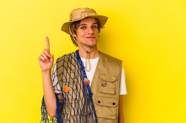 Jonge visser die met make-up een net houdt dat op gele achtergrond wordt geïsoleerd die nummer één met vinger toont.