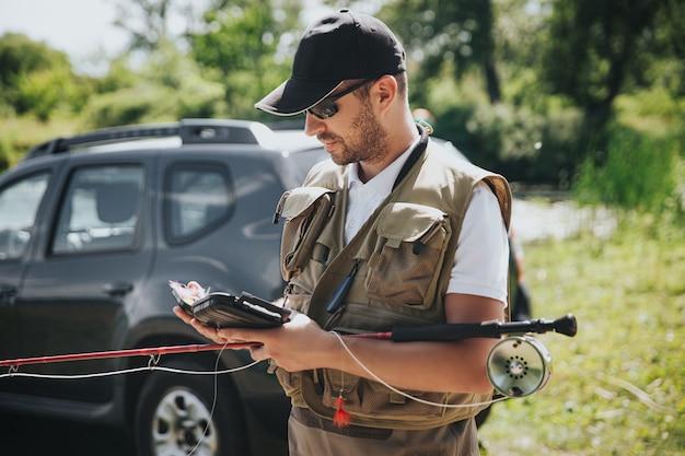 Jonge visser die op meer of rivier vist. drukke man met smartphone. ga bij de auto staan en houd de hengel vast voordat u begint met vissen. professionele visser.