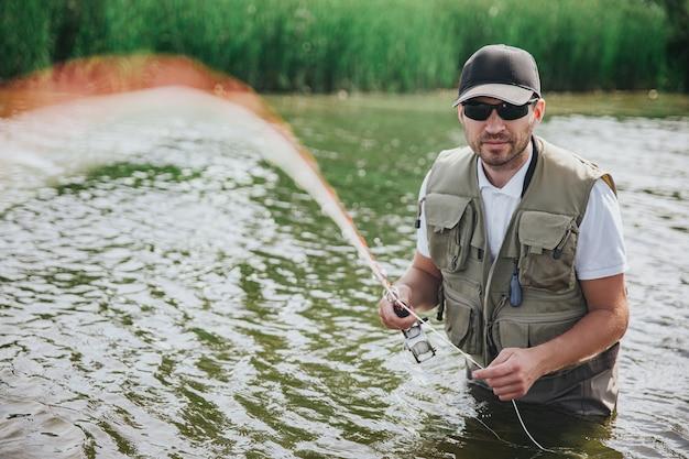 Jonge visser die op meer of rivier vist. ernstige geconcentreerde man in gewaad en zonnebril die recht op camera kijkt en vislijn in handen houdt die rechtstreeks naar camera gaan. zomertijd.
