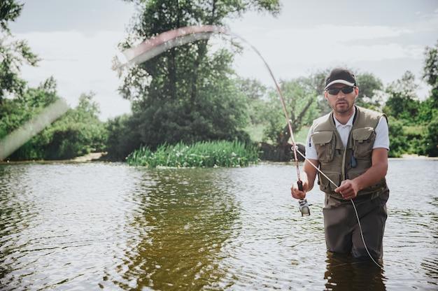 Jonge visser die op meer of rivier vist. ernstige geconcentreerde man in visserskleren staat in rivier- of meerwater en houdt een staaf vast. proberen smakelijke, heerlijke vis te vangen. hobby of levensstijl.