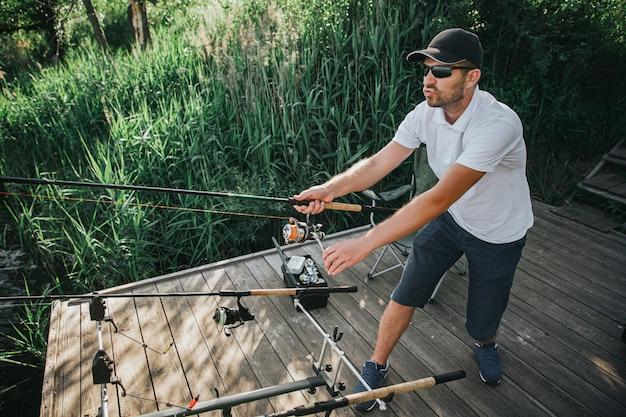 Jonge visser die op meer of rivier vist. foto van het visserijproces. guy twee hengels in handen houden en vissen. sta alleen bij de waterpier.