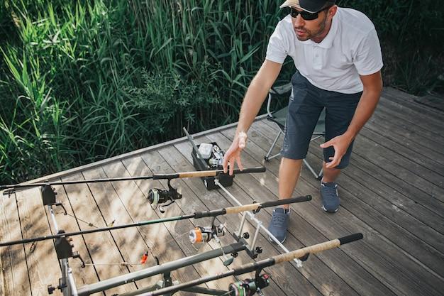 Jonge visser die op meer of rivier vist. guy hand reiken naar een van de hengels. ze aanpassen voor het vangen van riviervissen. sta alleen op de rivierpier. zonnige mooie dag.