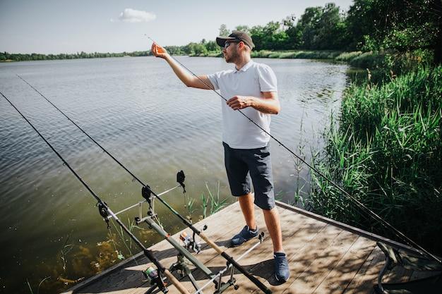 Jonge visser die op meer of rivier vist. kerel heeft drie hengels die vissen en vissen in water proberen te vinden. man bezig met het aanpassen van de staaf weer. alleen vissen in meer- of rivierwater.