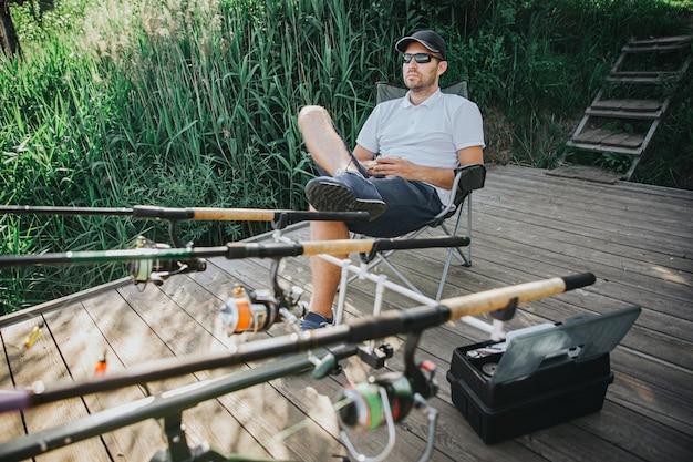 Jonge visser die op meer of rivier vist. ontspannen zittend in klapstoel voor drie hengels om te vissen. professionele visuitrusting. zittend aan de rand van een meer of rivier.