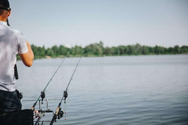 Jonge visser die op meer of rivier vist. snijd de weergave van een man die op een meer of rivier vist. met twee hengels. uitrusting aanpassen voor het visproces. mooie zonnige dag.