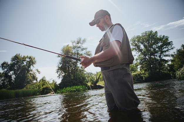 Jonge visser die op meer of rivier vist. volwassen man in visserskleren en pet met staaf in handen. lokaas gebruiken om vis te vangen. mand staat in rivier- of meerwater. mooie zonnige dag.