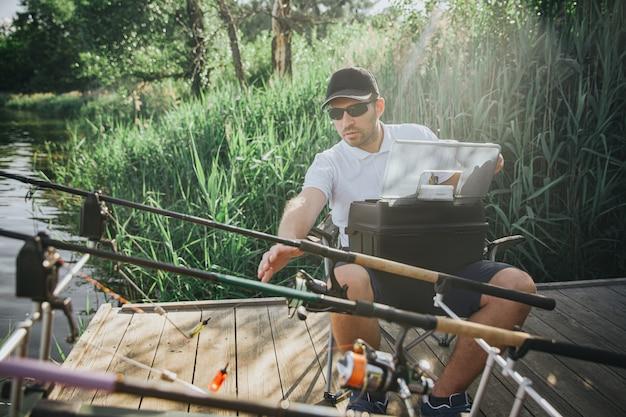 Jonge visser die op meer of rivier vist. volwassen man zit in een klapstoel en hand reikt naar een van de staven. maak je klaar om te vissen. uitrusting voor waterjacht aanpassen.