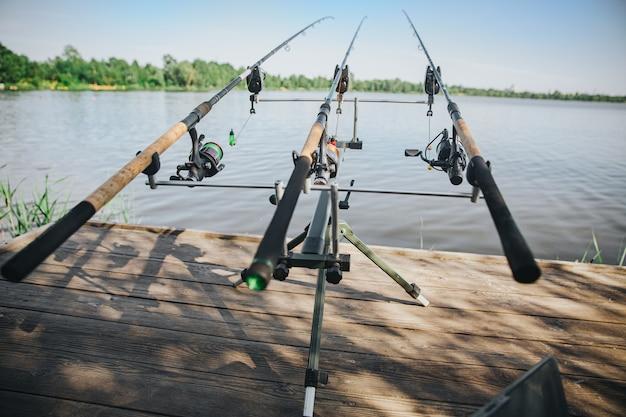 Jonge visser die op meer of rivier vist. vooraanzicht van drie hengels die zich op waterpijler zonder mensen bevinden. lege plek met zonneschijn en mooi weer. vistijd.
