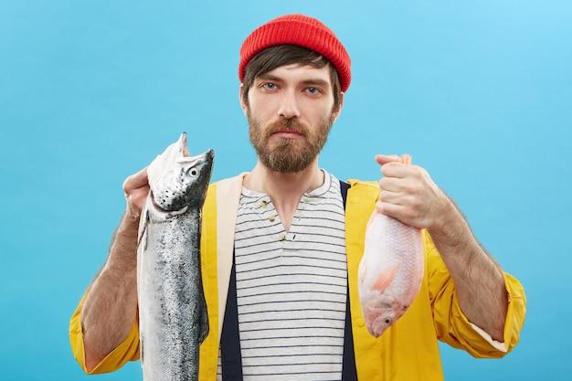 Jonge visser die twee vissen houdt