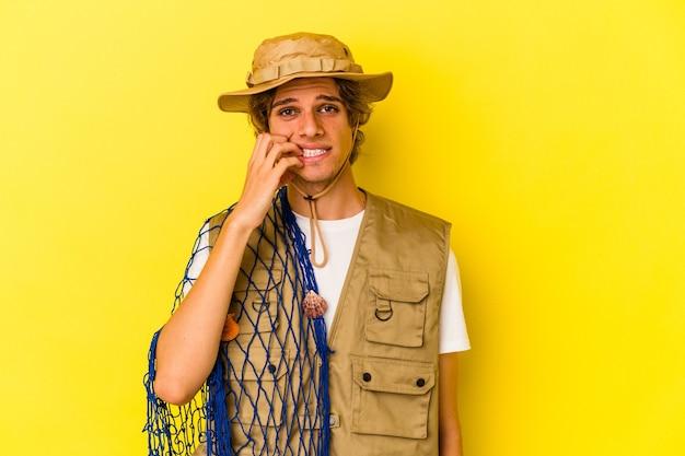 Jonge visser met make-up die een net houdt dat op gele achtergrond wordt geïsoleerd en vingernagels bijt, nerveus en erg angstig.