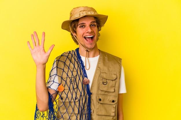 Jonge visser met make-up die een net houdt dat op gele achtergrond wordt geïsoleerd en vrolijk glimlacht die nummer vijf met vingers toont.